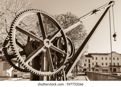 Gear wheels of an old and vintage crane. The crane is located near the small harbor on the lakeside of Luino, Lake Maggiore, Italy. Vintage tone, sepia color