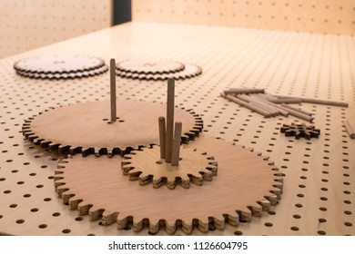 Gear wheels of wooden gears on a perforated table assembled together to form a mechanism. Educational activity for children, STEM subjects for engineering and mechanics at school