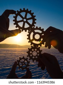 gears in the hands of a group of people against the setting sun. concept teamwork.