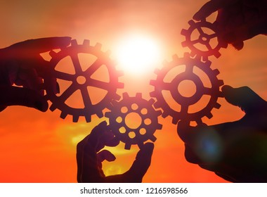gears in the hands of a group of people on the background of the evening sky. the concept of teamwork. interaction, mechanism.