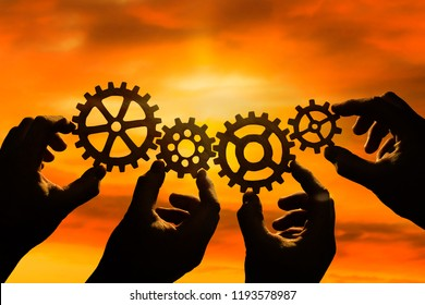gears in the hands of people against the evening sky. business interaction, mechanism, teamwork.