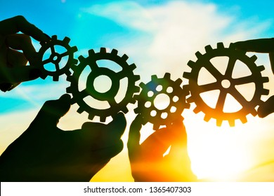 Gears in the hands of people against the sky. interaction, teamwork.