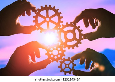gears in the hands of people on the background of the evening sky.business concept, teamwork.