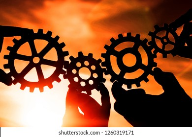 gears in the hands of people on the background of the evening sky. mechanism, interaction, teamwork.
