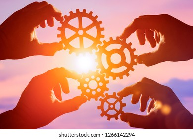 gears in the hands of people on the background of the evening sky, sunset. mechanism, interaction, teamwork.