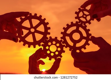 gears in the hands of people on the background of the evening sky. the mechanism of teamwork.