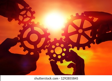 gears in the hands of people on the background of the evening sky. team work. interaction.