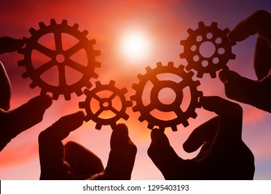 gears in the hands of people on the background of the evening sky. the concept of teamwork. the mechanism of interaction.