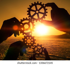 gears in the hands of people on the background of the evening sky. the mechanism of interaction, teamwork