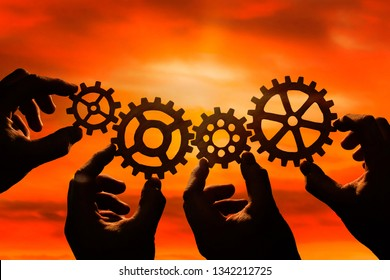 gears in the hands of people on the background of the evening sky. the concept of teamwork