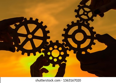 Gears in the hands of people on the background of the evening sky. teamwork, interaction.