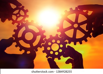 Gears in the hands of people on the background of the evening sky. teamwork, mechanism, interaction.