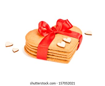 Geart-shaped gingerbread cookies tied up with red ribbon on white background