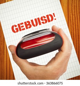 Gebuisd, failed in dutch language concept with rubber stamp in hand, paper and wooden table