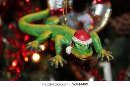 Gecko with Santa hat Christmas ornament with blurred tree with lights in background - selective focus.