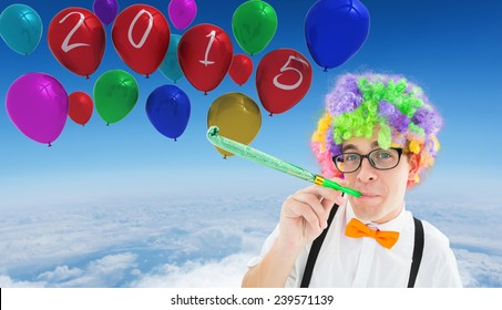 Geek blowing party horn against blue sky over white clouds