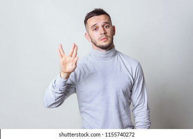 Geek saluting concept. Bristle men in white turtleneck shirt welcomes fans of fiction films Vulcan greeting on grey background copy space