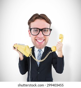 Geeky businessman holding phone against white background with vignette