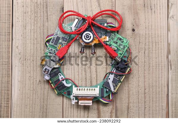 flor de Navidad geeky hecha con viejas piezas de computadoras colgadas en la puerta de madera, idea de reciclaje de partes de computadoras, diseño de tarjetas de Navidad