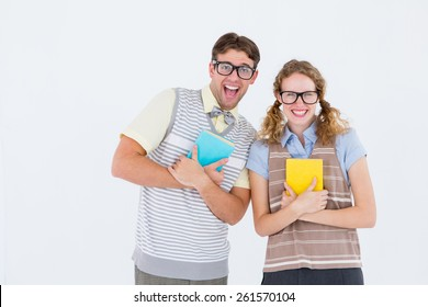 geeky hipster couple holding books and smiling at camera on white background
