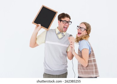 Geeky hipster couple singing into a microphone on white background