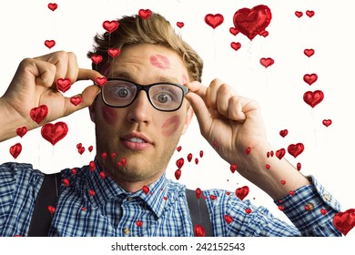 Geeky hipster covered in kisses against red heart balloons floating
