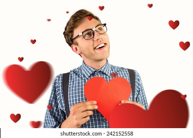 Geeky hipster holding a heart card against hearts