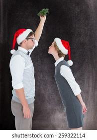 Geeky hipster kissing under mistletoe against black background