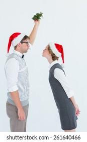 Geeky hipster kissing under mistletoe on white background
