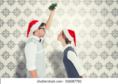 Geeky hipster kissing under mistletoe against grey wallpaper