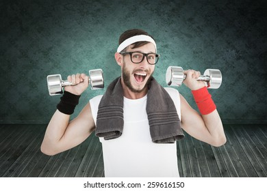 Geeky hipster lifting dumbbells in sportswear against green background with vignette