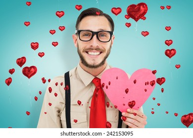 Geeky hipster smiling and holding heart card against blue vignette background
