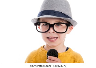 Geeky toddler boy talking in a microphone,  wearing big glasses and a hat. Studio shot isolated on white.