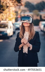Geeky young beautiful girl testing virtual reality 3D video glasses VR headset dressed in a office outfit impressed by augmented reality on the street and beautiful autumn sun light colors