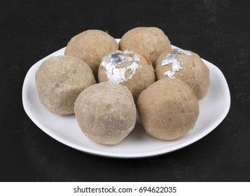 Gehu Ke Laddu Indian Traditional Sweet Food Also Know as Wheat Laddu, Laddoos, laddoo, ladoo, laddo Are Ball-Shaped Sweets Popular in The Indian Festivals. Laddu on Black Textured Background