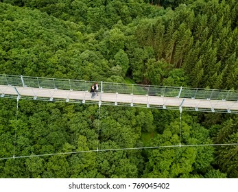 Geierlay, Morsdorf, Germany - July 11, 2017: Holidaymakers cross Germany's longest rope suspension bridge 300 feet above a canyon floor Geierley. It is between the towns of Morsdorf and Sosberg