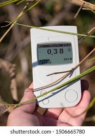 Geiger counter, dosimeter in hand close-up. Against the background of a bush. Summer is evening. Europe.