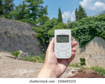 Geiger counter, dosimeter in the hand measures the background radiation. Summer, mountains, sky, old ruins of stone houses. Travel Europe.