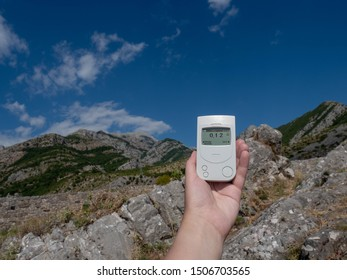 Geiger counter, dosimeter in the hand measures the background radiation in the open air in the mountains. Europe summer mountain landscape.