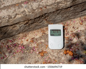 A Geiger counter, a dosimeter on stone steps measures background radiation. Summer, the old ruins of stone houses. Travel Europe.