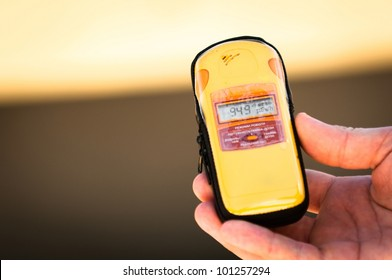 Geiger counter in hand with blurry background