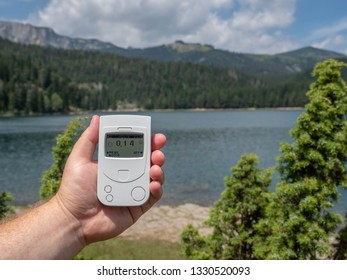 Geiger counter, radiation dosimeter in hand. Measures the background radiation of a mountain lake. Summer, reserve, mountain lake. Europe.
