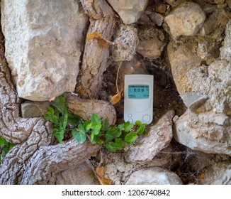 The Geiger counter, a radiation dosimeter, measures the radiation background of the ruins of the old city. Stone masonry. Europe.