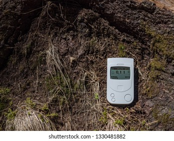 A Geiger counter, a radiation dosimeter, measures the background radiation of a forest soil. Mountain Reserve. Europe.
