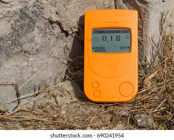 Geiger counter, a radiation dosimeter that measures the radiation background of a concrete foundation block.