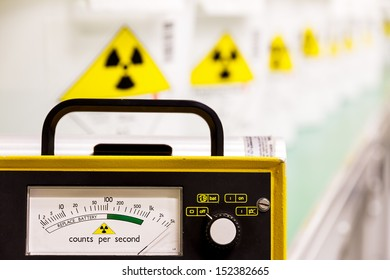 Geiger counter with radioactive materials in the background