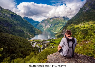 Geiranger Fjord Beautiful Nature Norway, a UNESCO World Heritage Site. Nature photographer tourist with camera shoots. The fjord is one of Norway's most visited tourist sites.