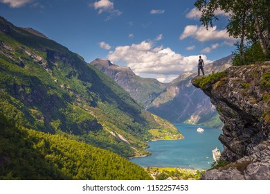 Geiranger - July 30, 2018: Traveler at Flydalsjuvet viewpoint looking down at the stunning UNESCO Geiranger fjord, Norway