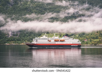 GEIRANGER, NORWAY - AUGUST 2016: Hurtigruten MS Nordnorge arriving Geiranger at rainy and foggy day.