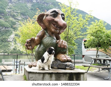 Geiranger / Norway - August 26 2018: Huge Troll statue. Big white and black dog next to the troll, where troll holds leash of the dog. Looks like one is walking with another. Happy and funny scene.